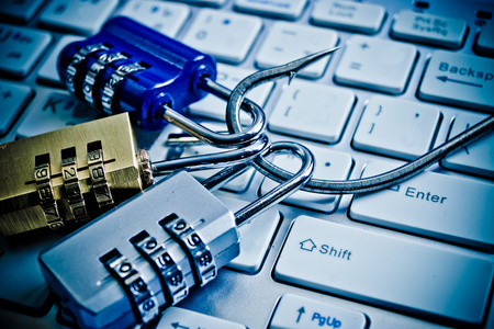 security breach: security locks with a fish hook on computer keyboard  security breach concept  phishing