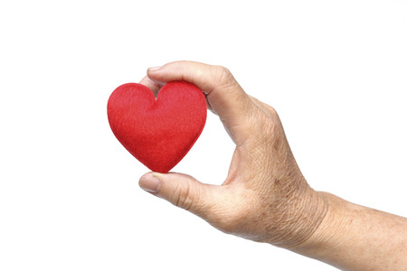 hand of the elderly female holding a red heart photo
