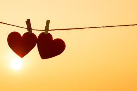 parejas: corazones rojos colgados de la cuerda con la silueta de la puesta del sol