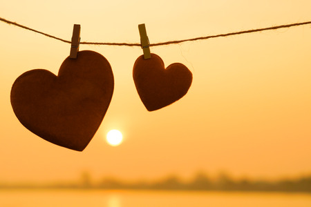 string together: Love for Valentines day - Two red hearts hung on the rope together with sunset silhouette