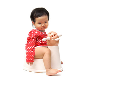 vasino: Asian child on potty play - learning to use toilet