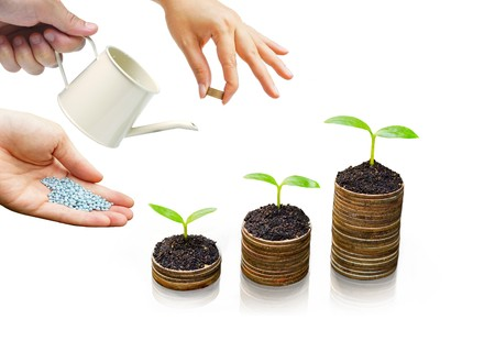 bucket of money: hands helping to grow trees on piles of golden coins  business with csr practice Stock Photo