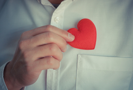 man business oriented: Businessman pulling out a red heart from the pocket of his suit - customer relationship management - service mind