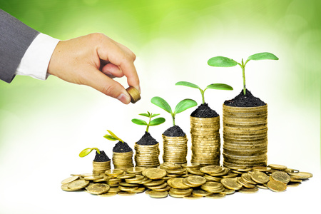 growing business: Hands of businessman giving coins to trees growing on coins in germination sequence  Business with csr practice