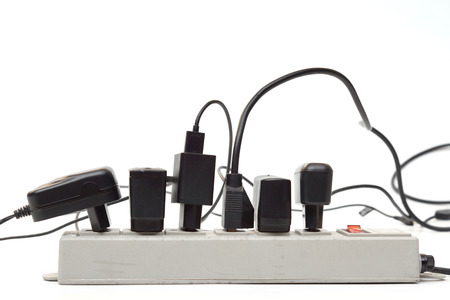 adapters: Many plugs and adapters plugged into electric power bar Stock Photo