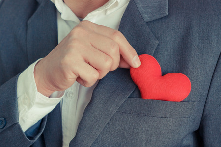 Businessman pulling out a red heart from the pocket of his suit - crm - service mind Standard-Bild