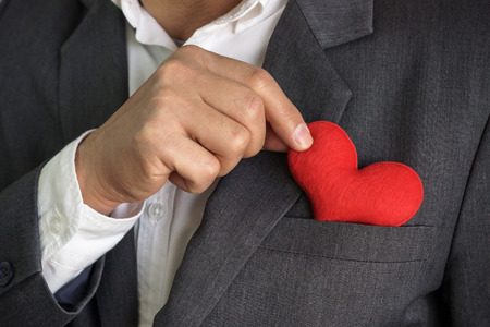 relationship love: Businessman pulling out a red heart from the pocket of his suit - crm - service mind Stock Photo