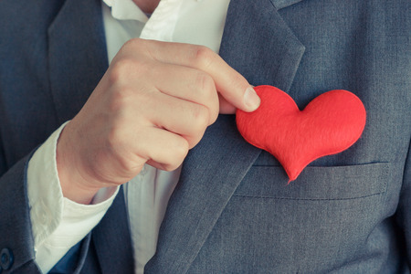 Businessman pulling out a red heart from the pocket of his suit - crm - service mind Stok Fotoğraf
