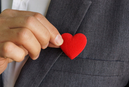 responsibility: Businessman pulling out a red heart from the pocket of his suit - crm - service mind Stock Photo