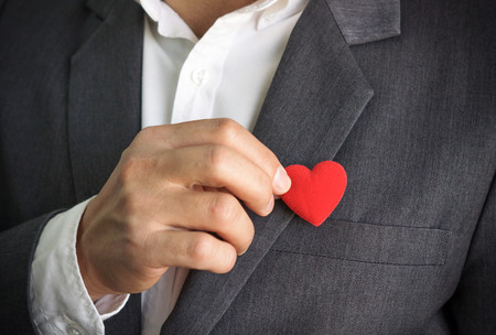 Businessman pulling out a red heart from the pocket of his suit - crm - service mind Stock Photo