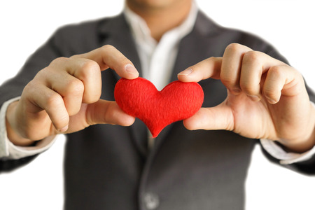 customer relationship: Businessman giving a red heart to a customer on isolated background