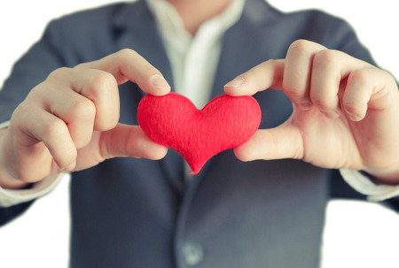 hands of a businessman holding a red heart  service mind Stock Photo
