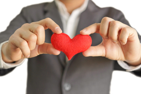 man business oriented: hands of a businessman holding a red heart  service mind Stock Photo
