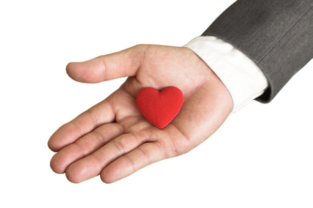 Businessman giving a red heart to a customer on isolated background - service mind