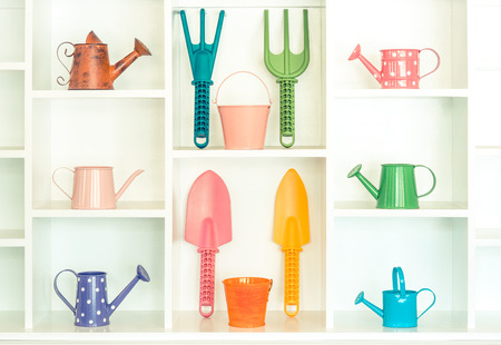 white shelf: colorful gardening tools on white shelf - fork, shovel, rake, bucket, watering can Stock Photo