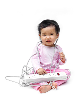 the surge: a young baby playing with electricity wire of a surge protector