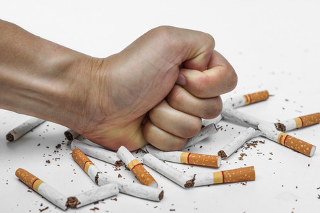 destroying: male hand destroying cigarettes - stop smoking concept