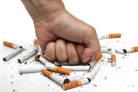 smoking stop: male hand destroying cigarettes - stop smoking concept