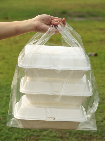 plastic waste: hands holding a clear plastic bags containing three foam containers