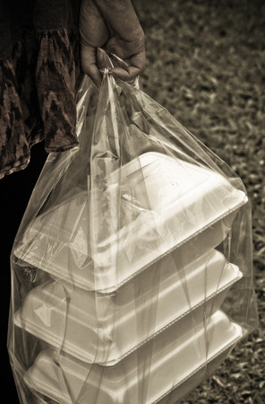a clear plastic bags containing three foam containers on green grass background
