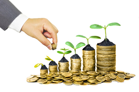 environmental concern: Hand of a businessman giving coins to a tree growing on golden coins - Business with csr practice and environmental concern