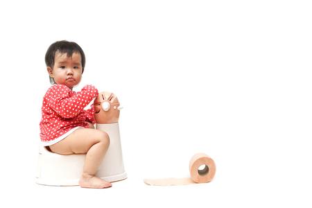 pis: asiático bebé usando y jugando con inodoro Foto de archivo