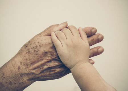 old hand: hand of a young baby touching old hand of the elderly Stock Photo