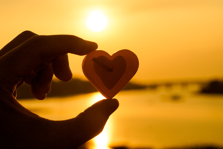 scented candle: hand holding a scented candle with a heart shape in sunset silhouette background