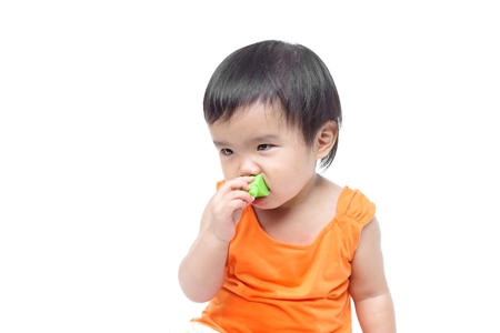 baby isolated: A young baby trying to put a small piece of toy into his mouth - The danger of young baby swallowing or eating little things concept