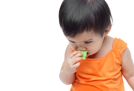 'young things': A young baby trying to put a small piece of toy into his mouth - The danger of young baby swallowing or eating little things concept