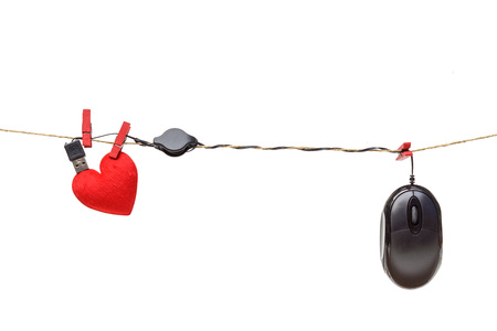 hung: online dating - a computer mouse hung on the rope with a red heart Stock Photo