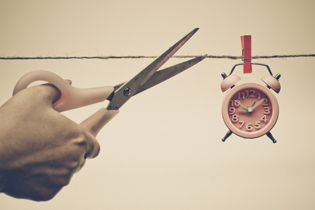 punctuality: hand cutting a rope with a clock hung on by a wooden clip - importance of time Foto de archivo