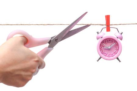punctuality: corte de una cuerda con un reloj colgado en la mano por un clip de madera - importancia del tiempo