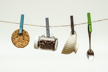 hung: A biscuit, a bottle of coffee beans, a spoon, and a cup hung on rope with wooden clips - Coffee time  Time to have a break