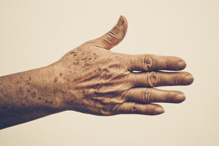 80 plus years: old female hand full of freckles with vintage tone Stock Photo