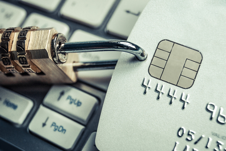 secured payment: security lock on credit cards with computer keyboard