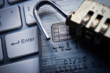 data theft: broken security lock with pile of credit cards representing credit card data theft