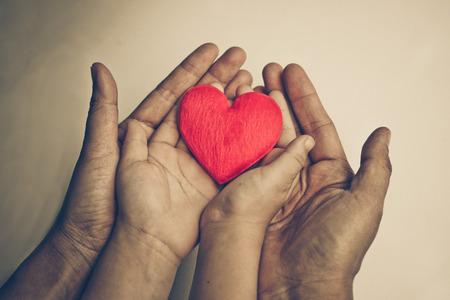 oude hand van de ouderen en een jonge hand van een baby die een rood hart samen