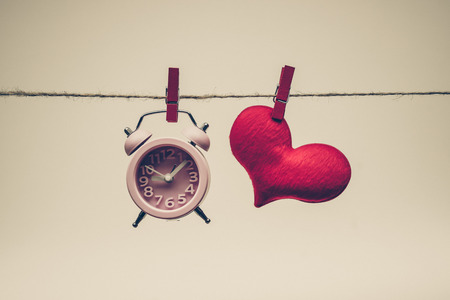 hung: A clock and a red heart hung together on a rope  time and love concept Stock Photo