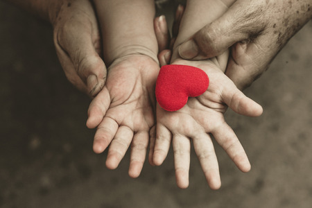 female hand: old hands holding young hand of a baby with red heart