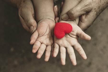 apoyo familiar: viejas manos que sostienen la mano joven y de un bebé con el corazón rojo