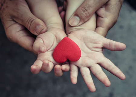 old hands holding young hand of a baby with red heart