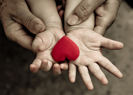 holding family together: old hands holding young hand of a baby with red heart