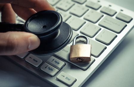 hand holding a stethoscope over computer keyboard with a security lock - computer system check and maintenance concept Foto de archivo