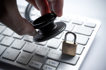 the lock: hand holding a stethoscope over computer keyboard with a security lock - computer system check and maintenance concept Stock Photo