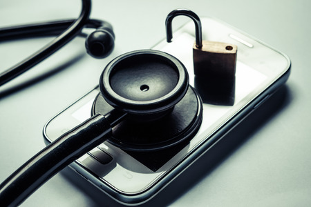 health care: stethoscope on smartphone - checking security on smartphone concept Stock Photo