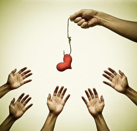 deceive: many hands trying to catch a red heart on a fish hook - Love trap concept