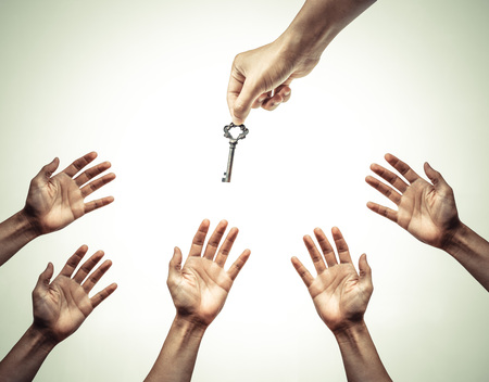 key to success: hand giving a key to many hands - giving help, opportunity, success concept Stock Photo
