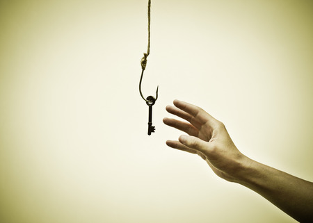 opportunist: hand reaching out trying to get a key on a fish hook - The victim of success concept Stock Photo