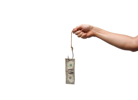 deceive: hand holding a dollar banknote hung on a fish hook - money trap concept
